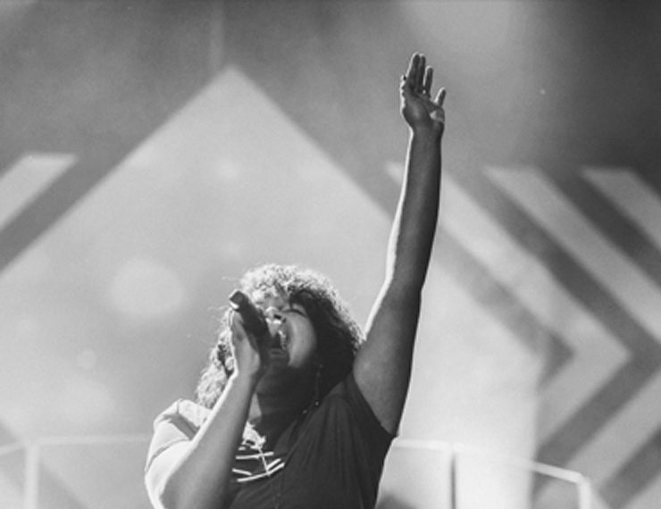 Woman singing on stage and raising arm